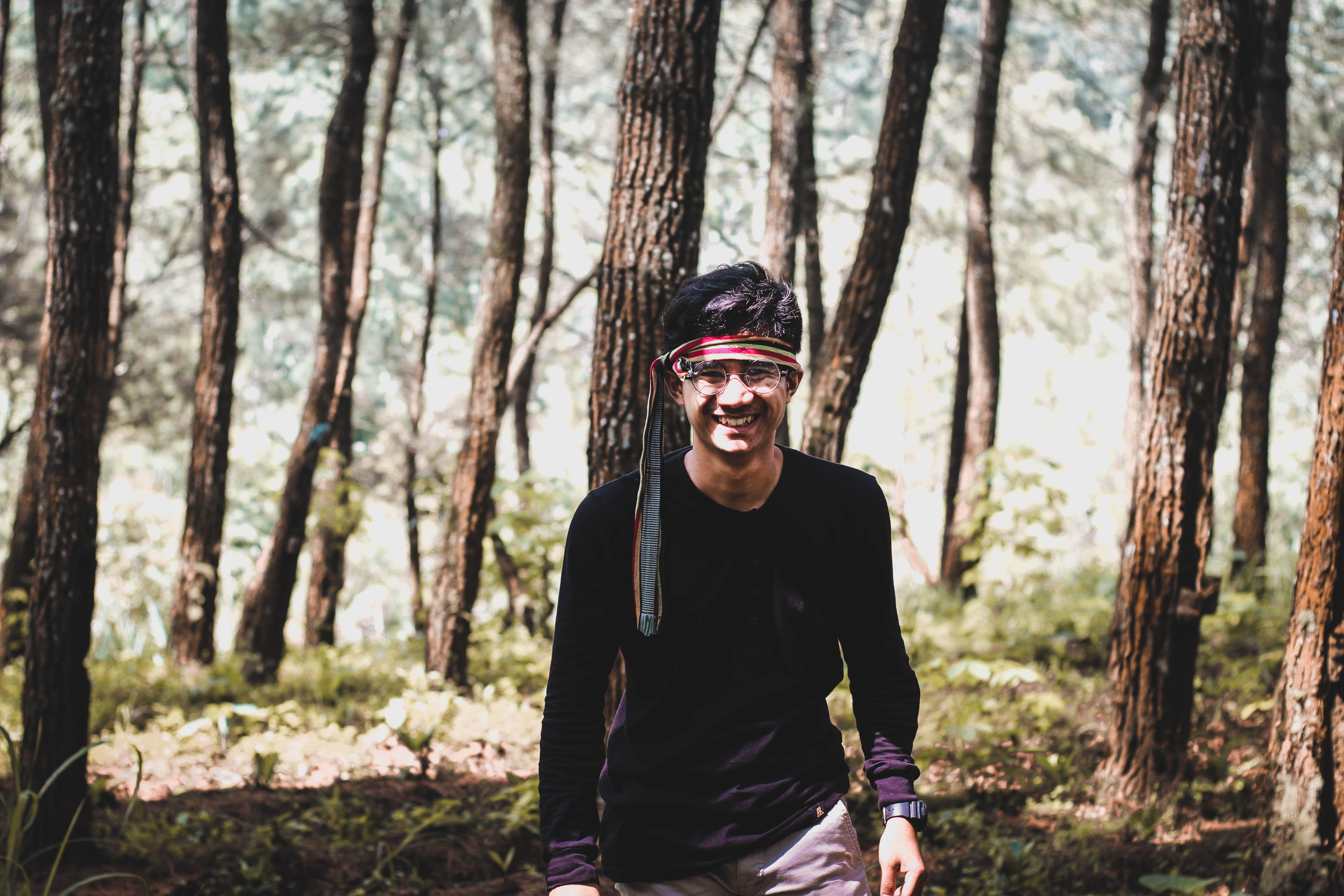 man wearing black shirt walking inside forest