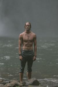 man wears black pants stands on rocks near body of water