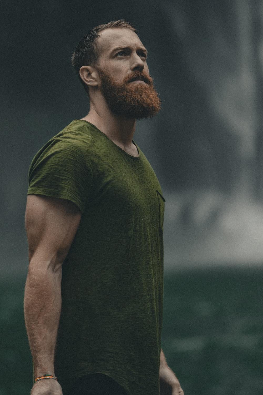 man wearing green crew-neck t-shirt looking upwards