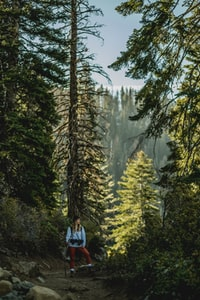 woman in white jacket with red pants standing near tree during daytime