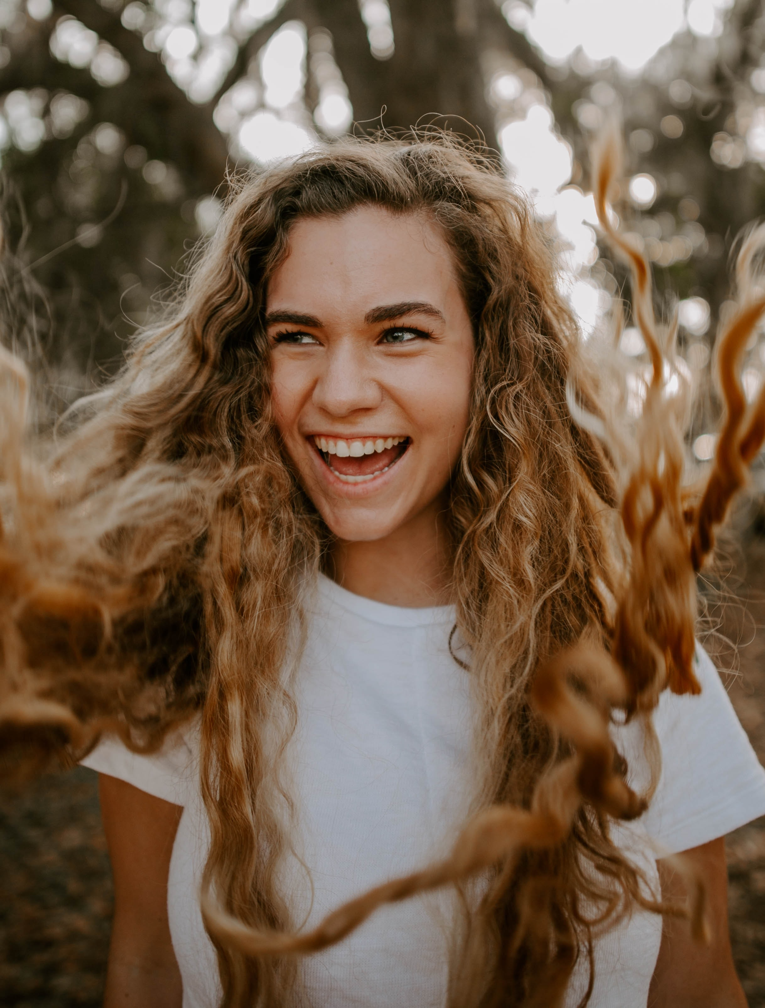 selective focus photo of laughing girl wearing white crew-neck shirt