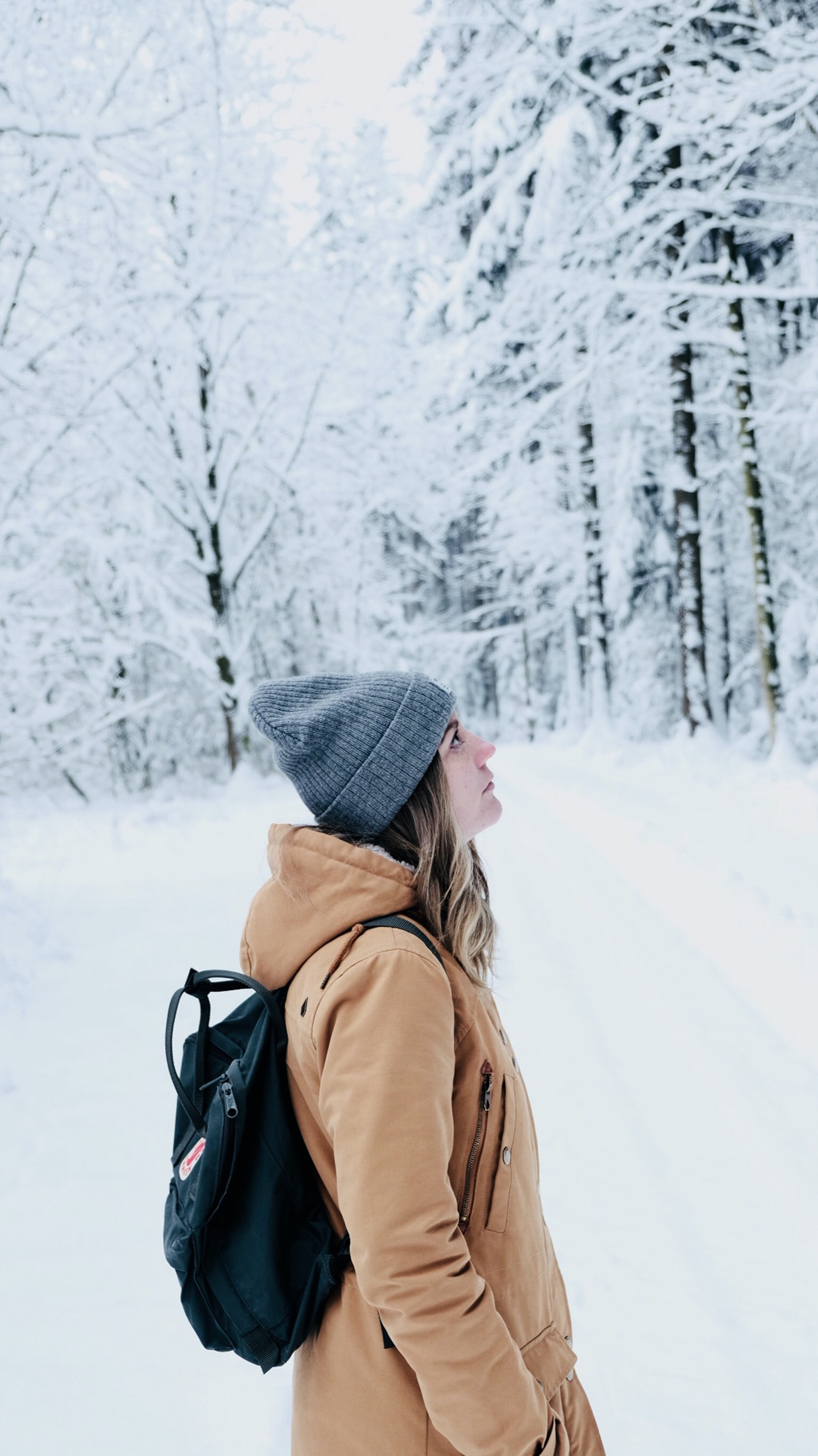 woman walking in snow covered forest