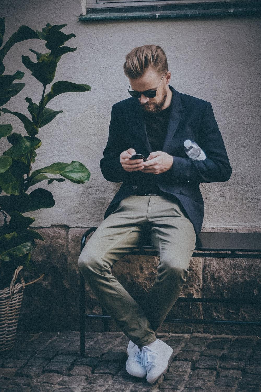 man using smartphone sitting on black metal bench near brown concrete wall