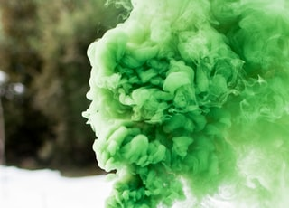 shallow focus photography of canister producing green smoke