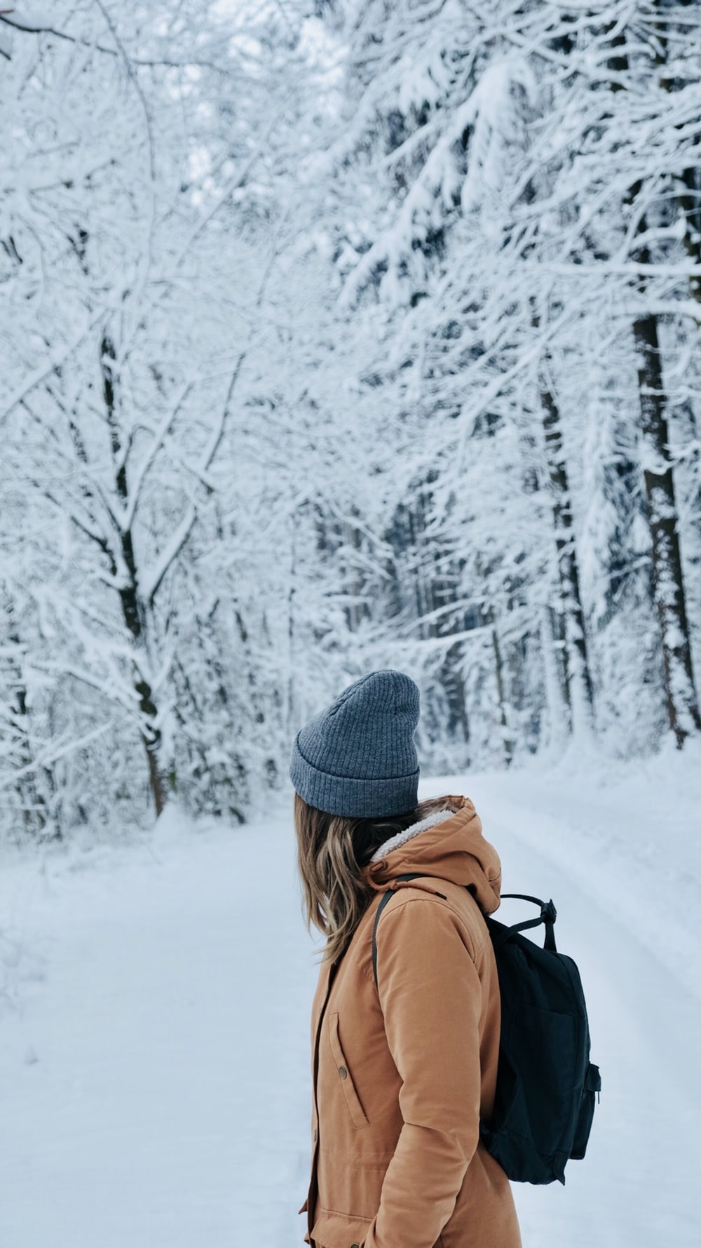 shallow focus photography of woman standing on snow field looking her backj