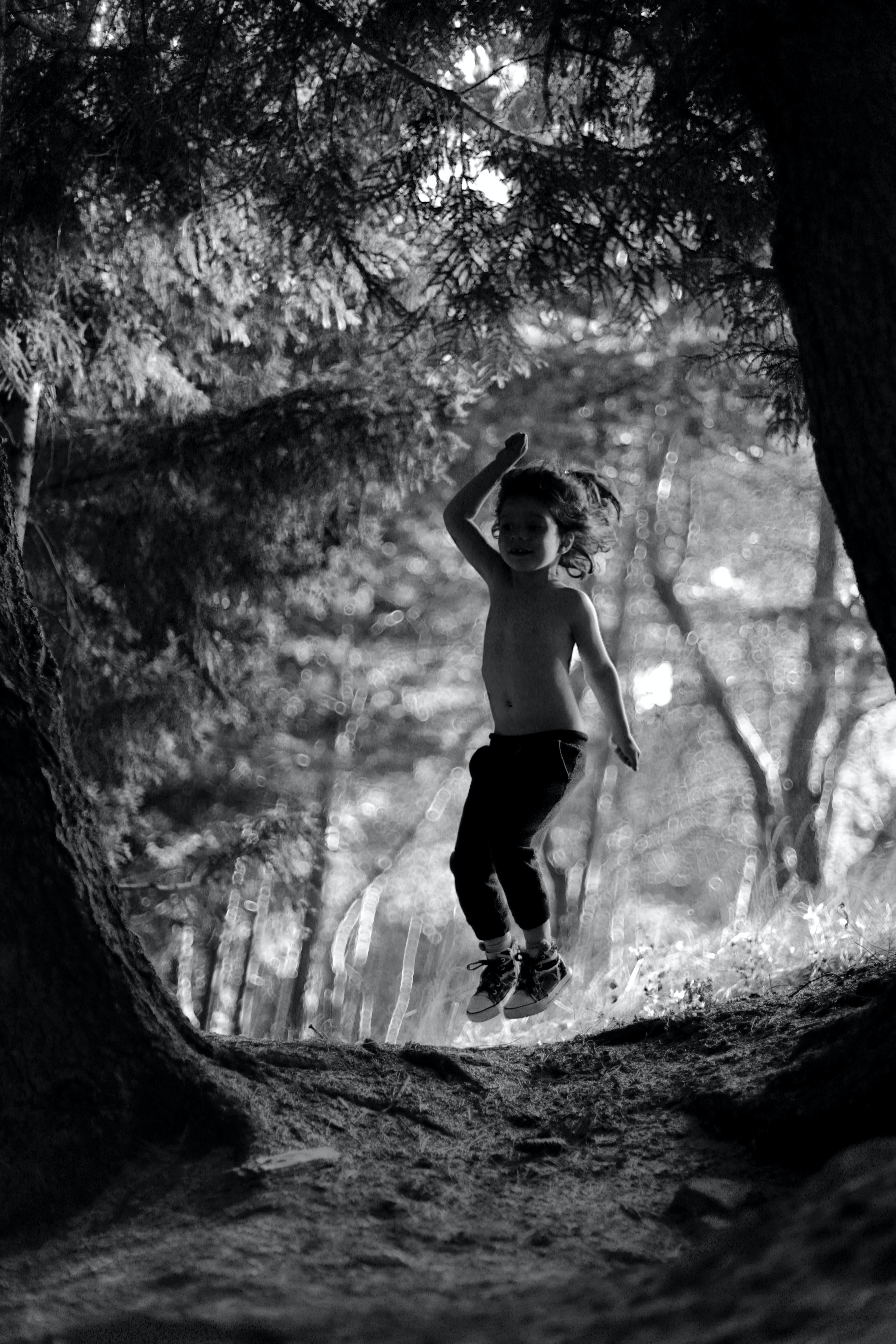 greyscale photo of child jumping near trees