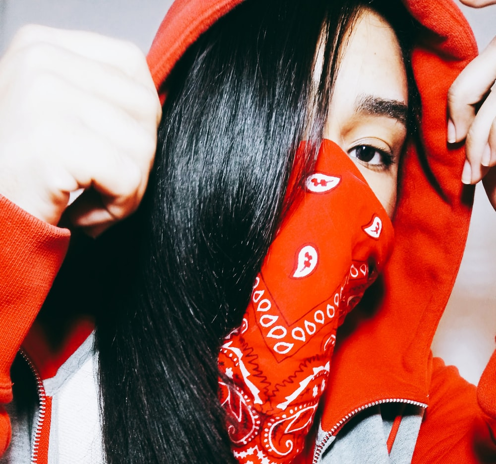 woman wearing red and white paisley scarf taking close-up selfie