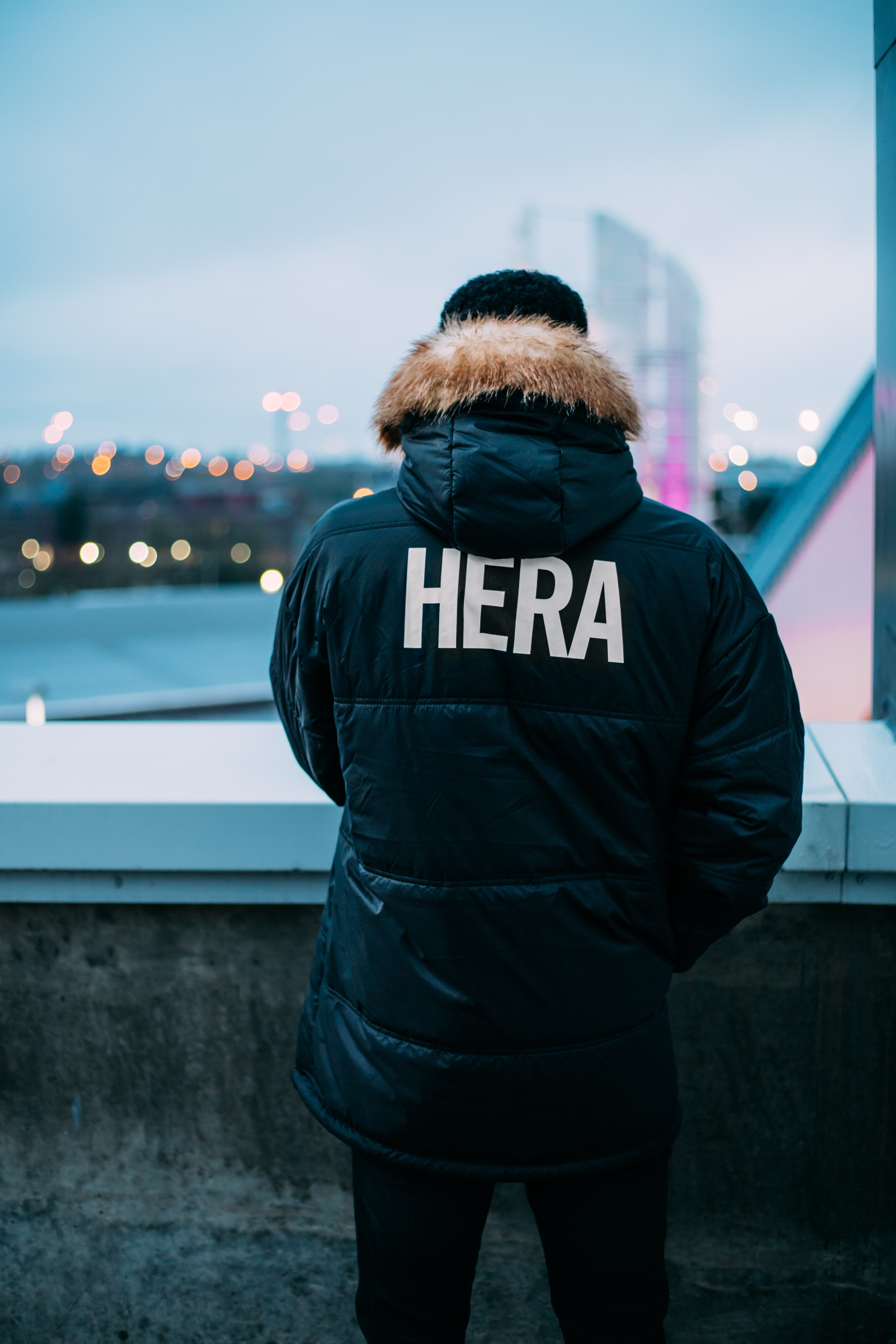 person wearing black and brown parka jacket with Hera-printed text standing facing the cities