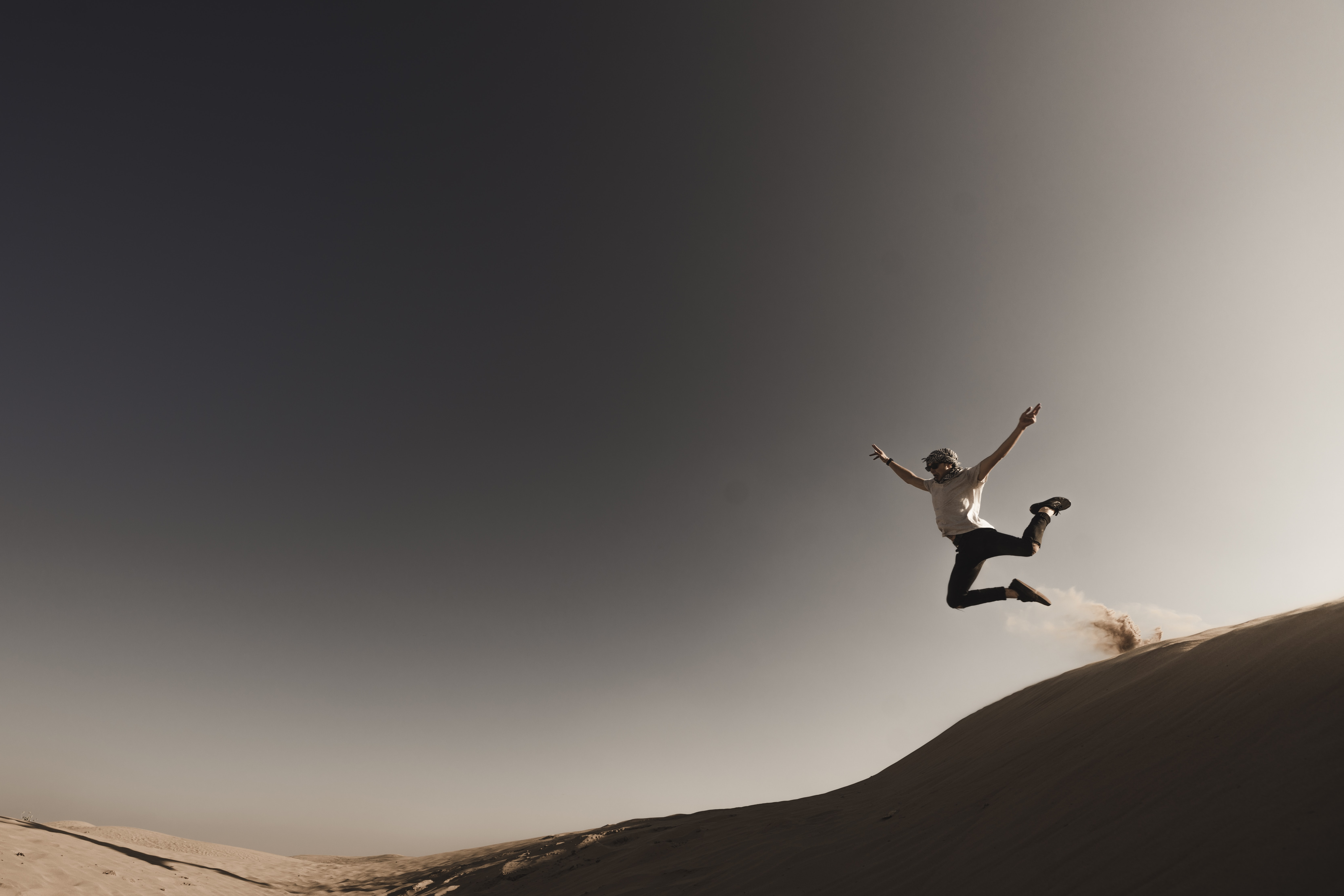 person jumping from sand dune during daytime