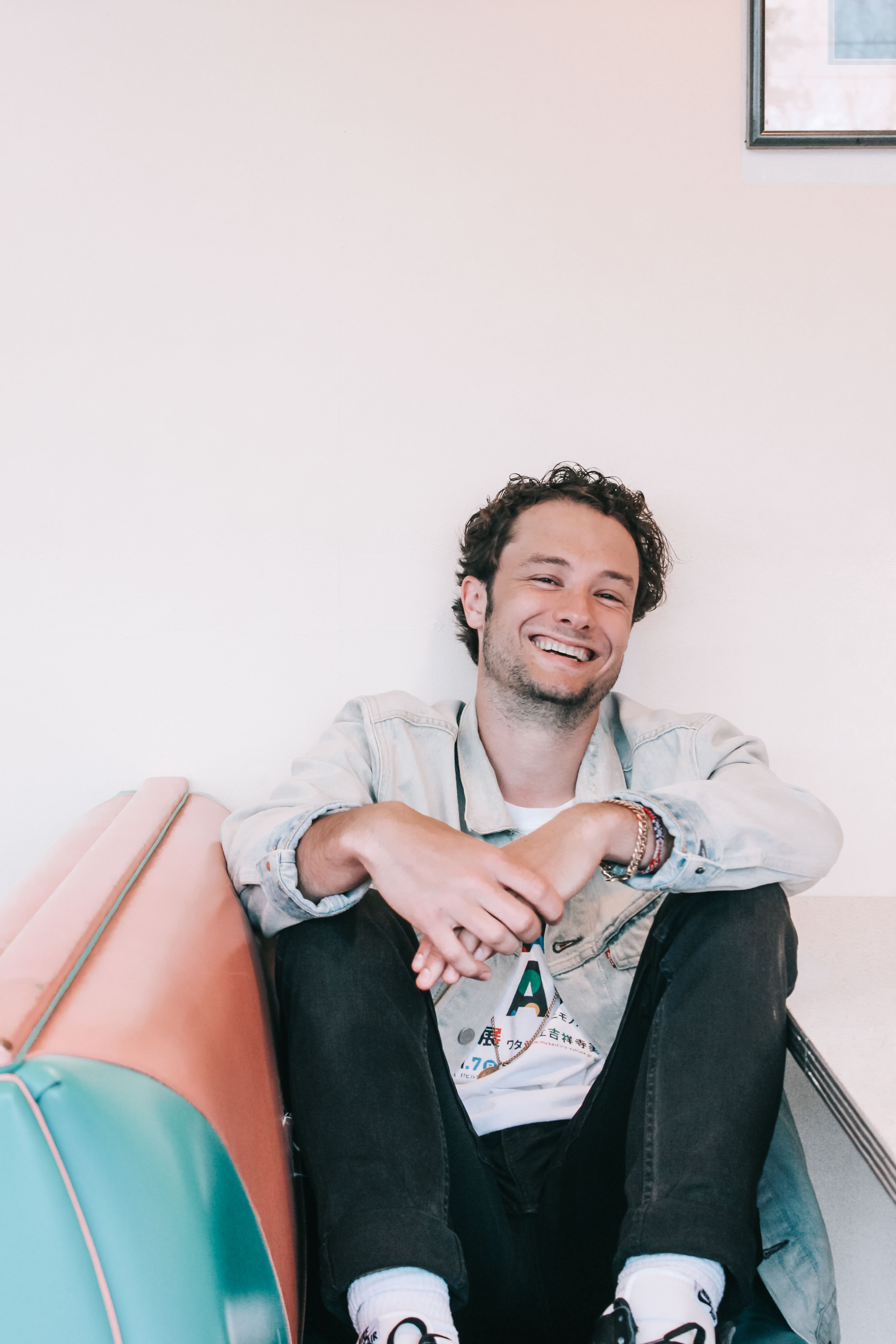 man smiling sitting on sofa leaning on wall