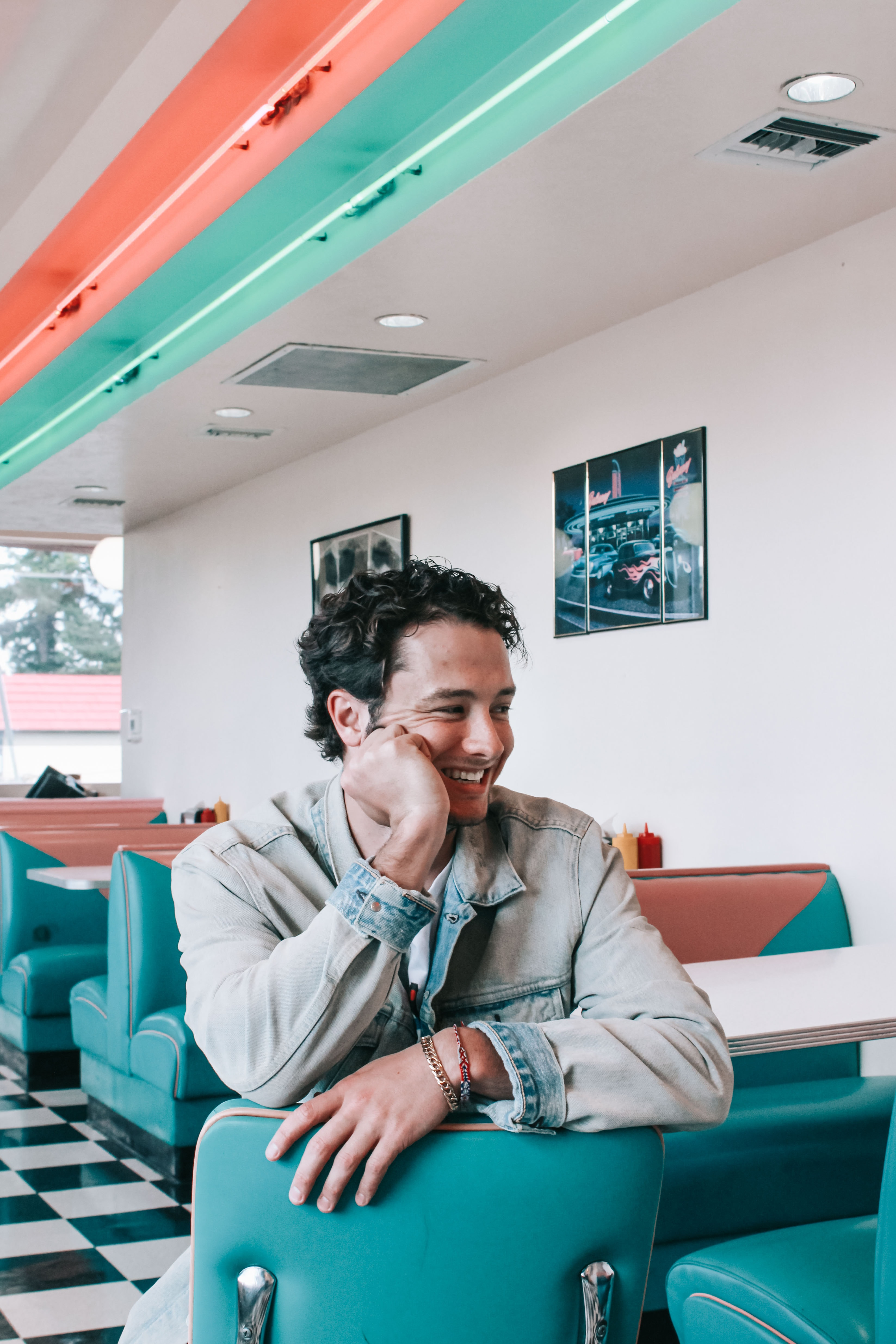 smiling man wearing gray denim jacket sitting on green leather chair beside white wooden dining table