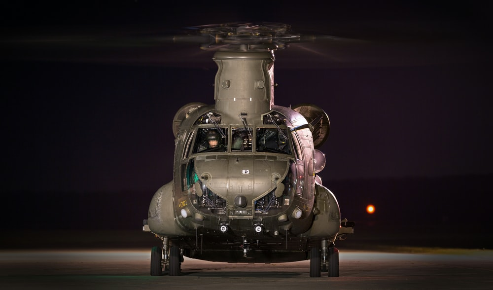 gray helicopter on land at night time
