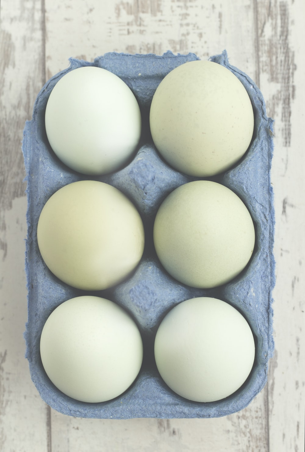 six white eggs placed on gray tray