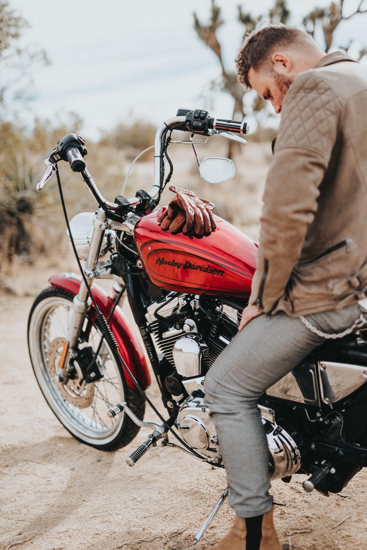 man sits on red and black Harley-Davidson motorcycle during daytime