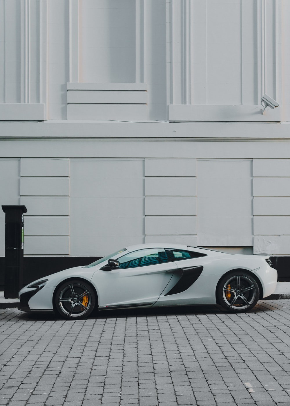 white and black coupe beside white building paint