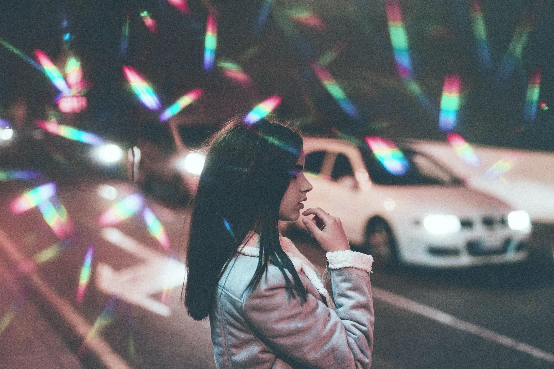 girl standing near white car on road