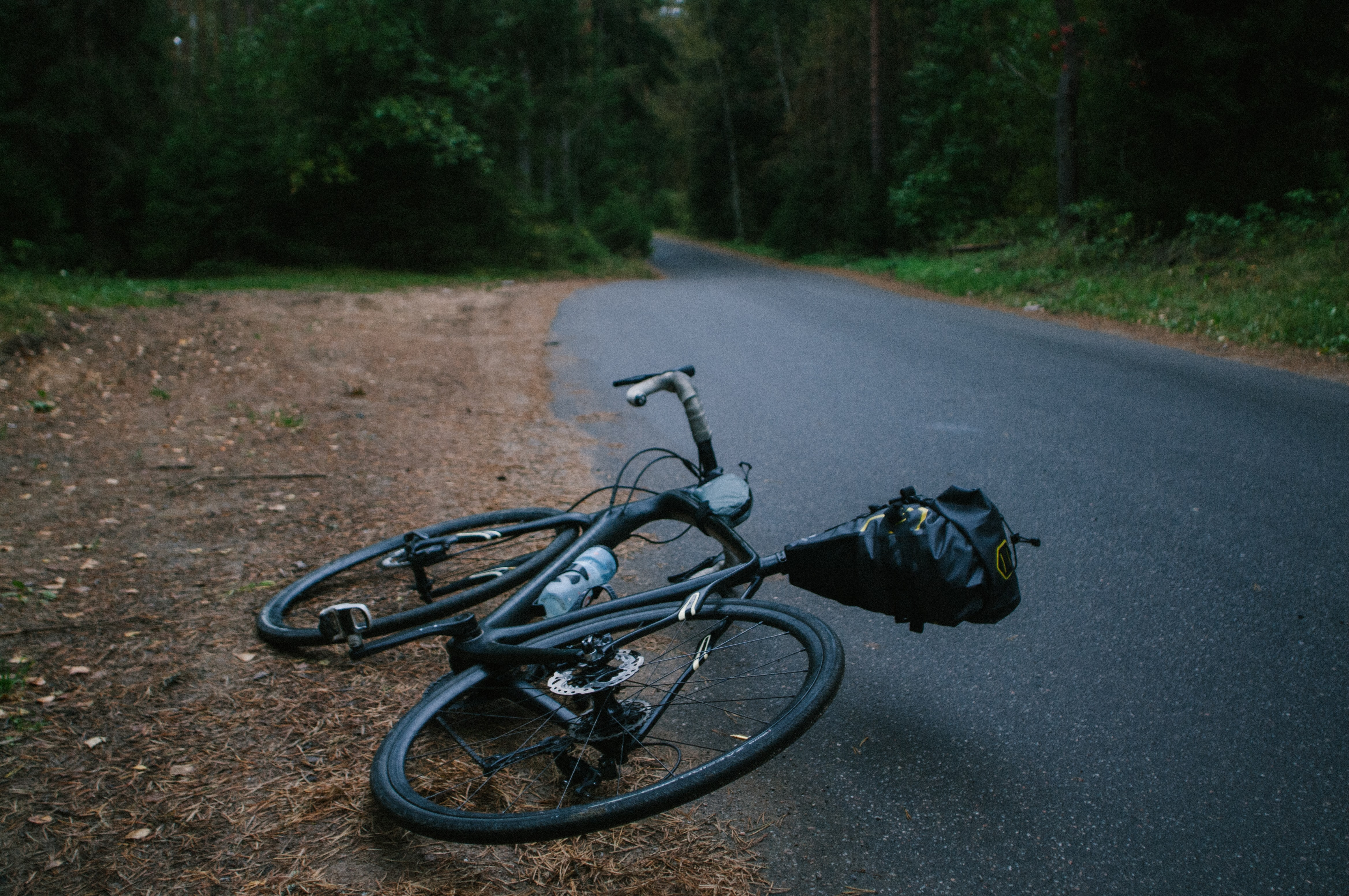 black road bike lying on asphalt road during daytime
