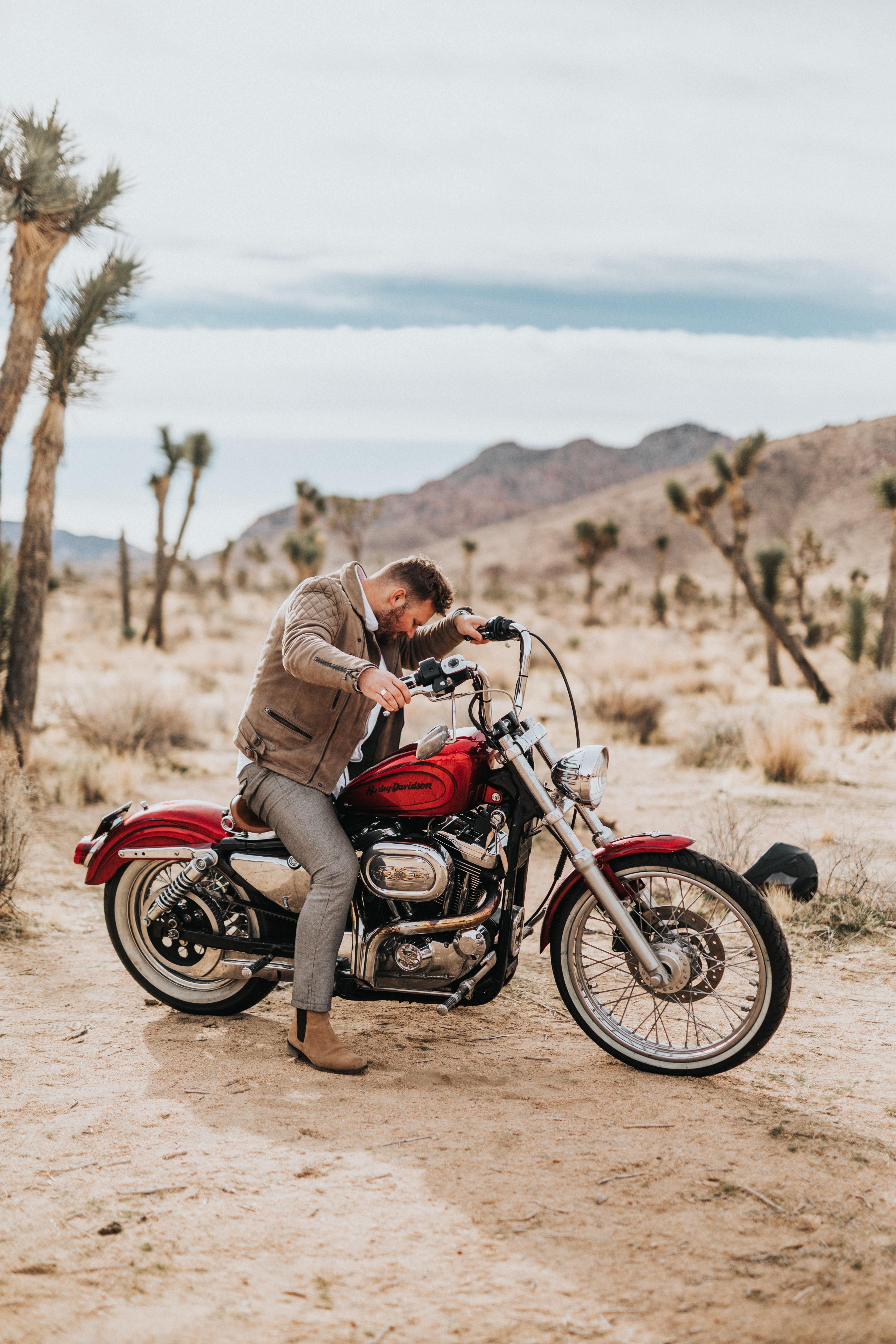 man riding red cruiser motorcycle