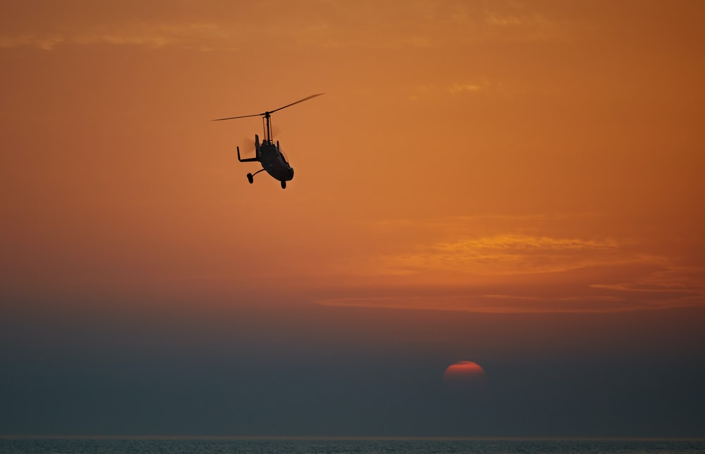 silhouette of helicopter flying during sunset