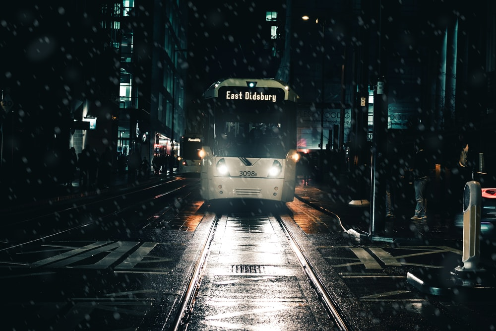 white bus on street during rain