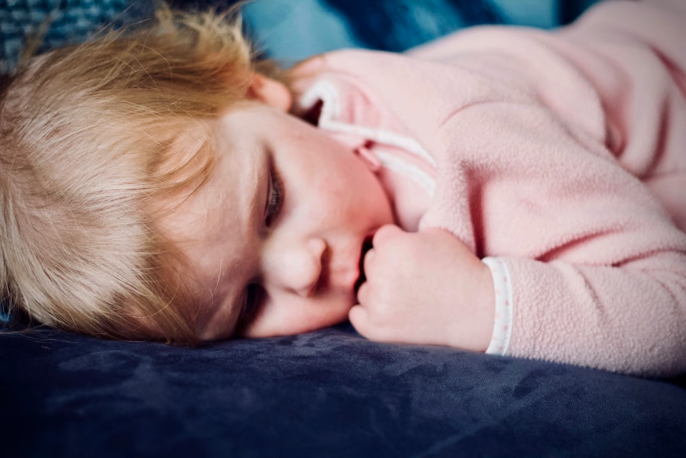 baby sleeping on black surface