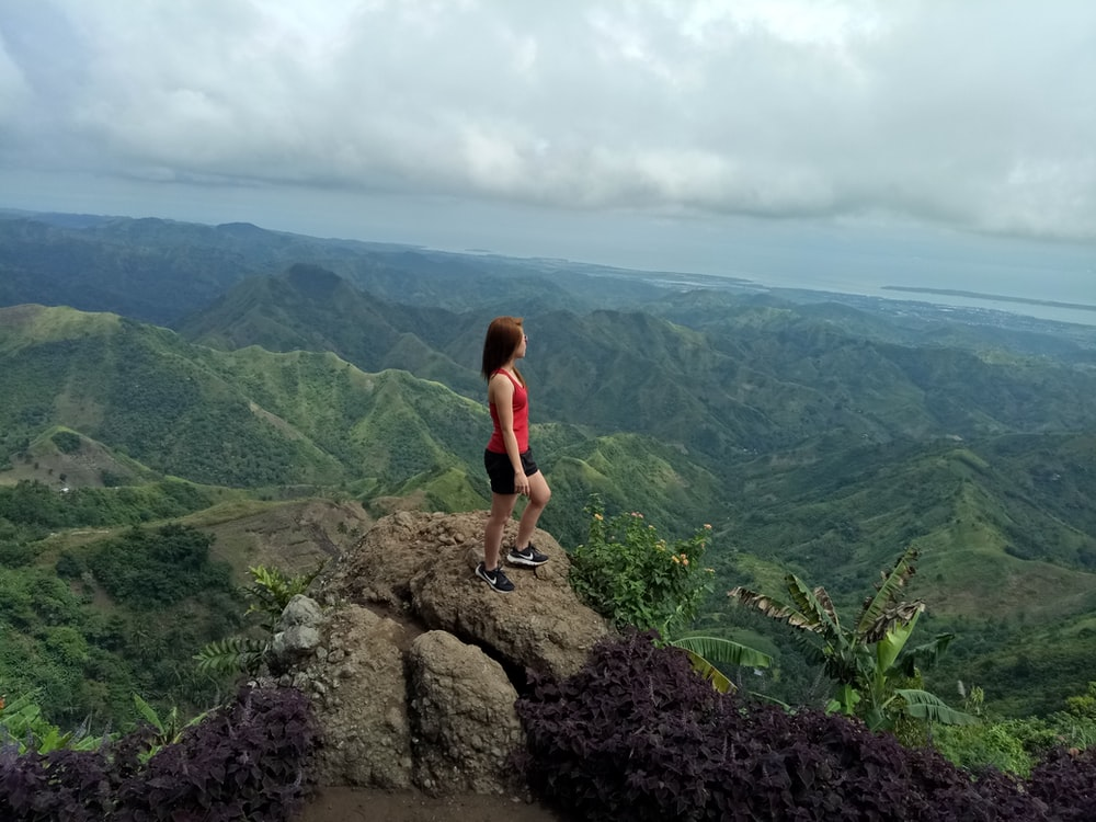 woman in red tank top standing on rock formation during daytime