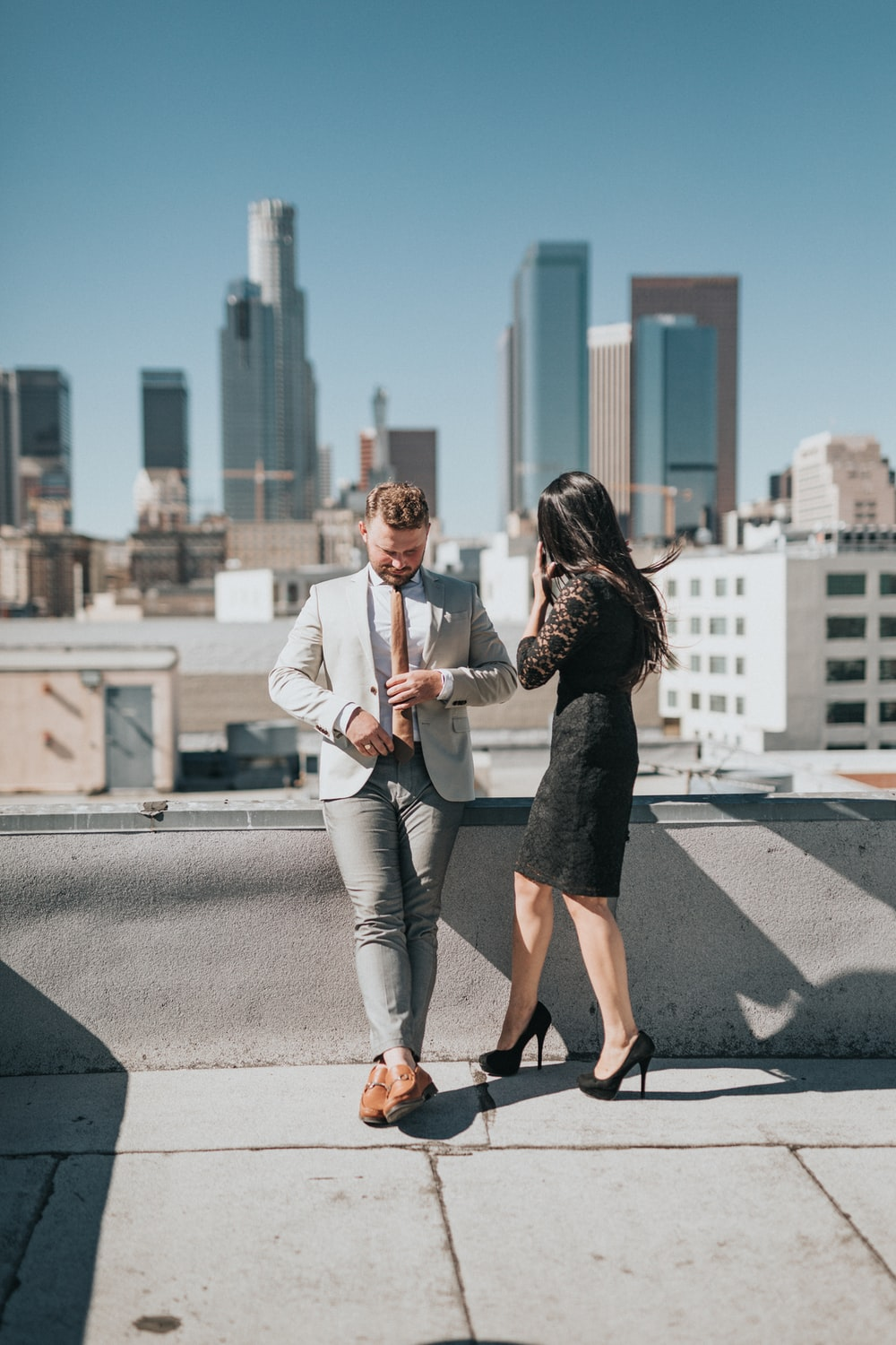 man and woman standing on rooftop of building during daytime