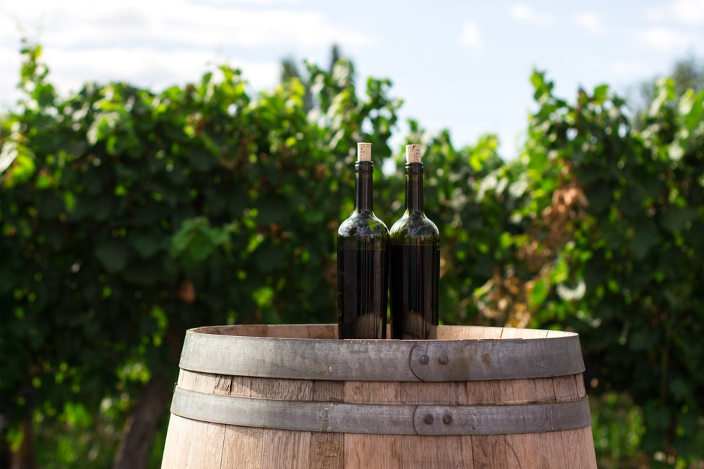 two black glass bottles on the top of the brown wooden barrel