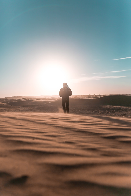 person standing on desert land