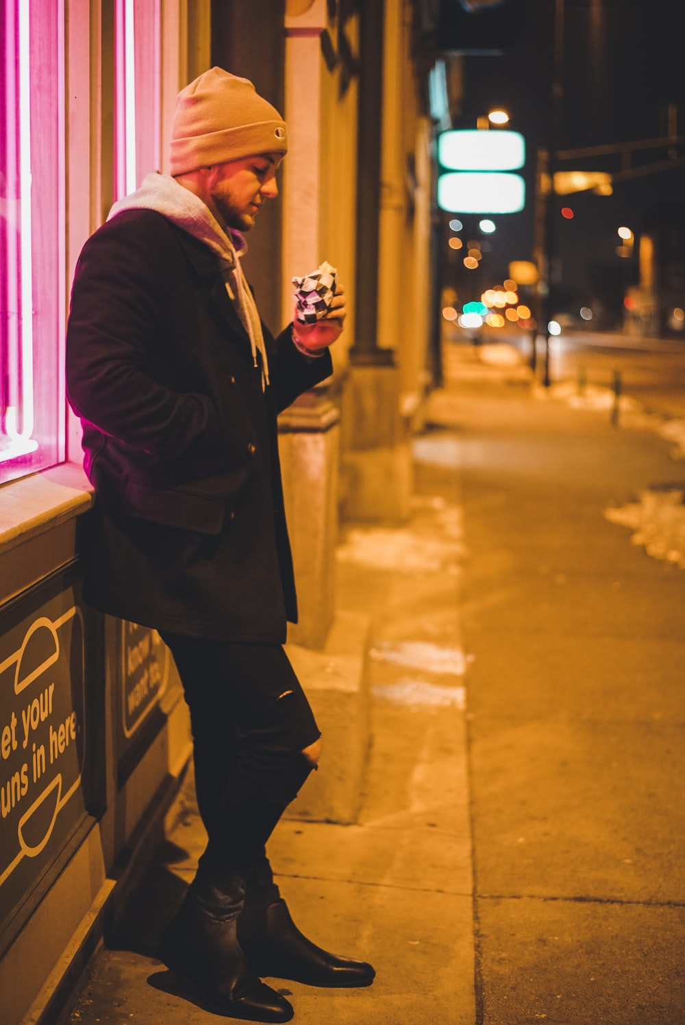 man leaning on wall while holding pack during night