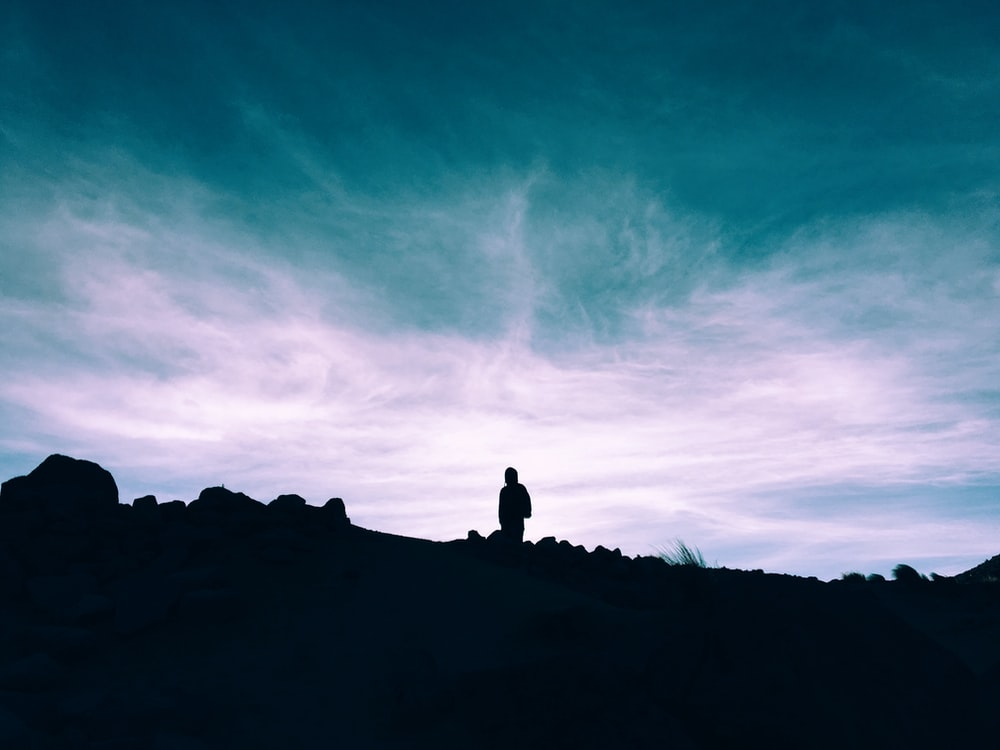 silhouette of man standing on ground under blue and white sky