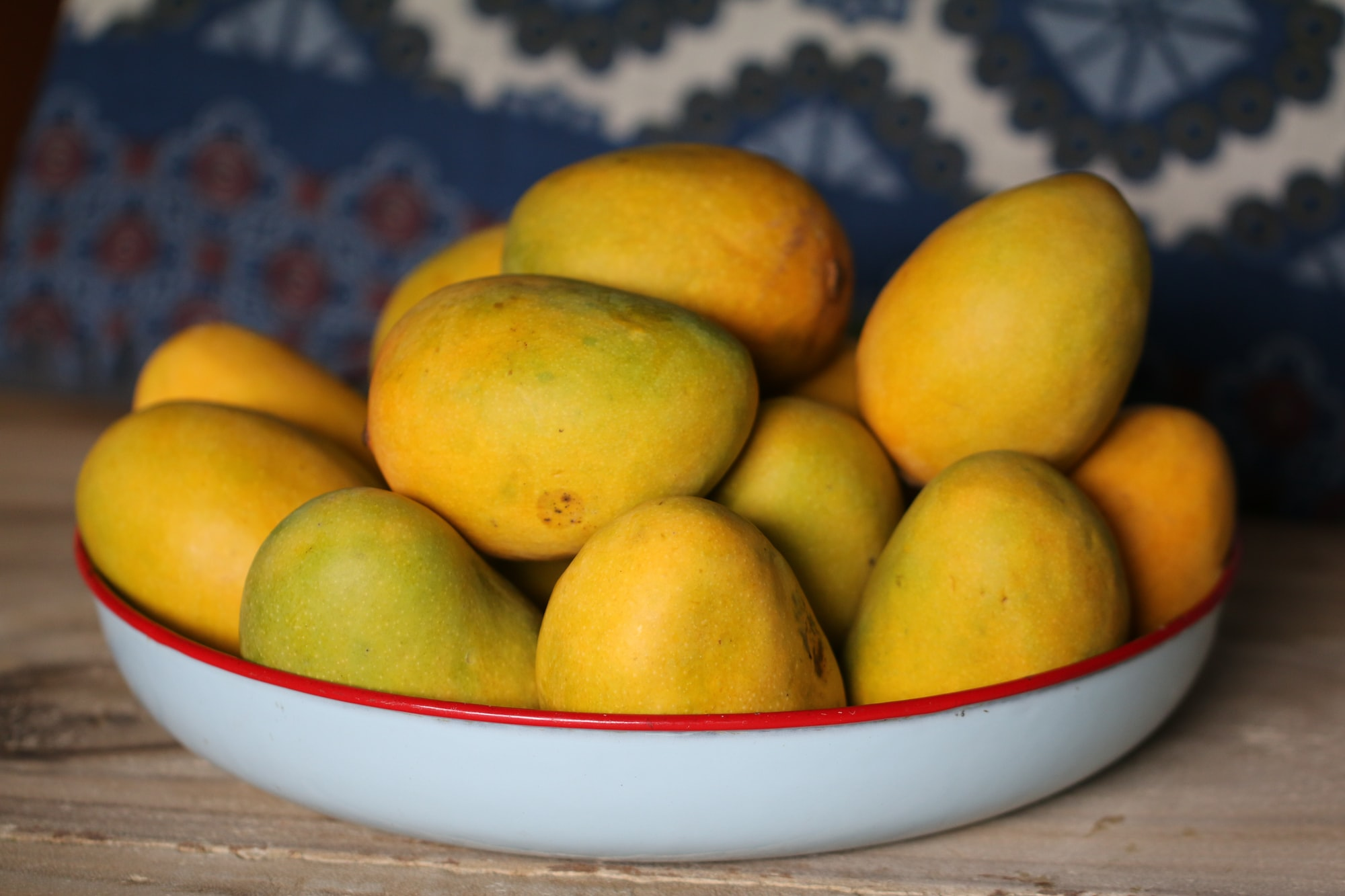 A wide bowl with a red rim is filled with yellow mangoes