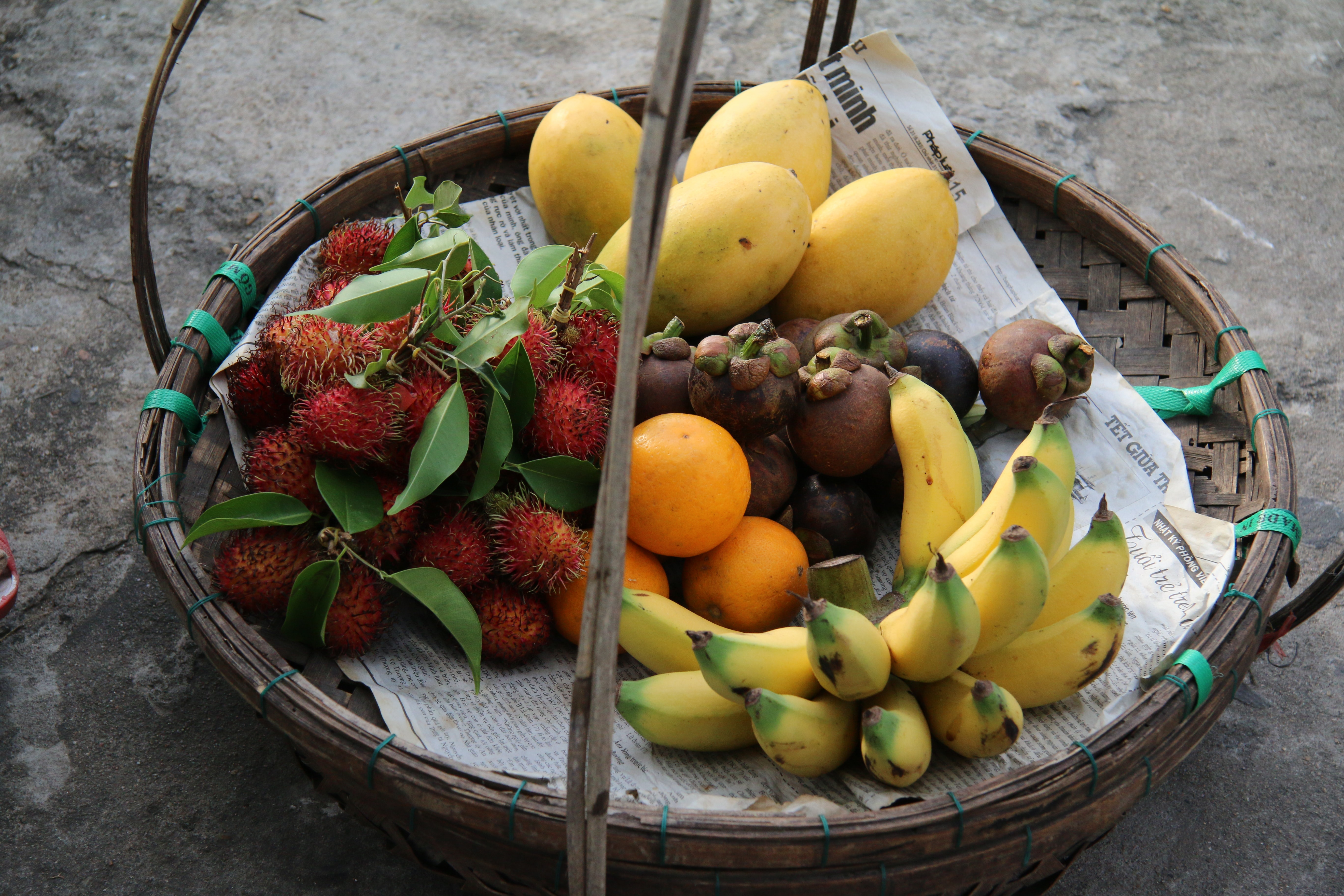 basket of yellow bananas, yellow mangoes, red rambutan fruits, oranges, and mangosteen fruits