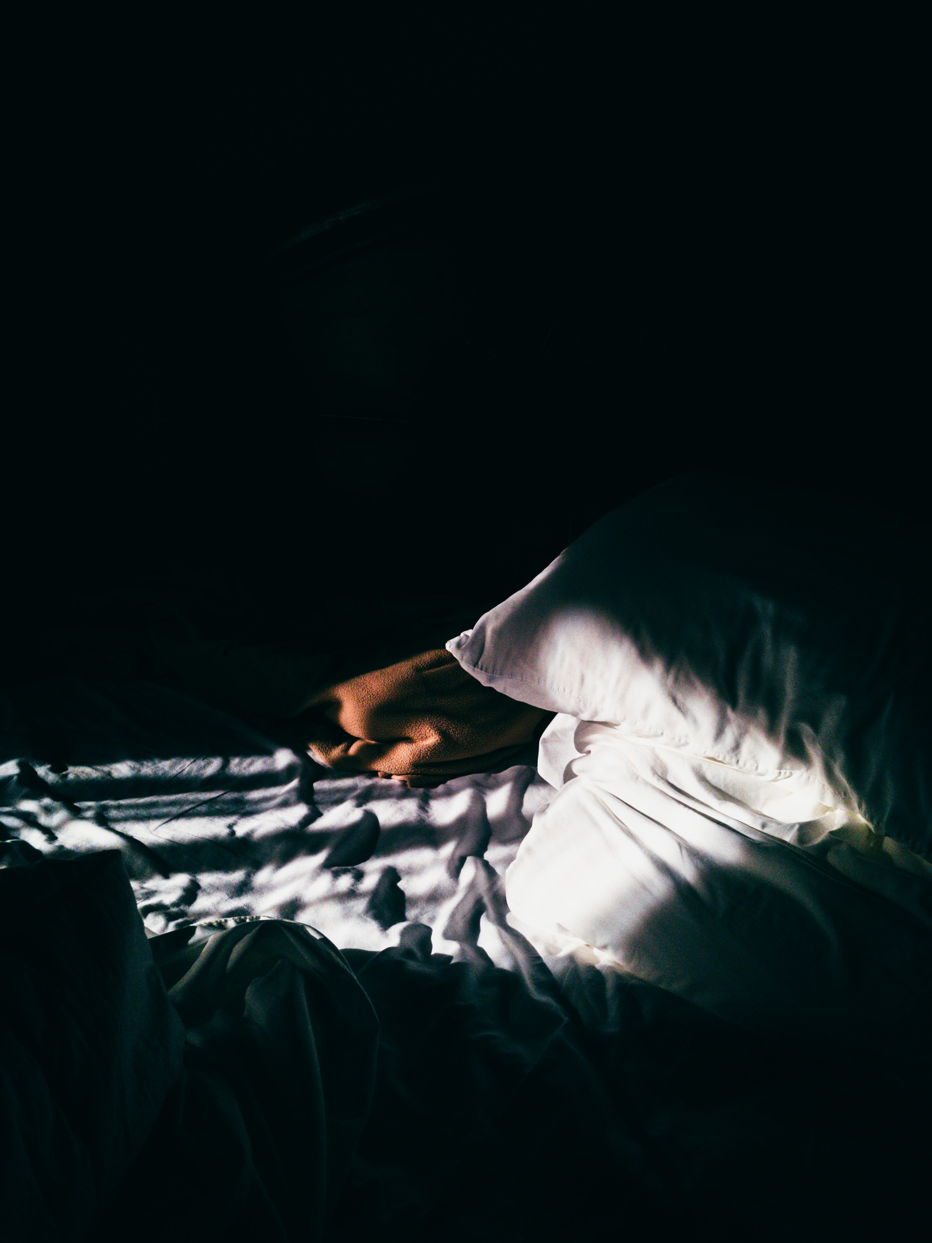 gray throw pillow on gray bedspread