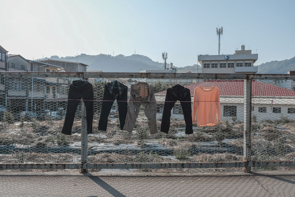 four assorted pants and orange shirt hanging on gray cyclone wire fence