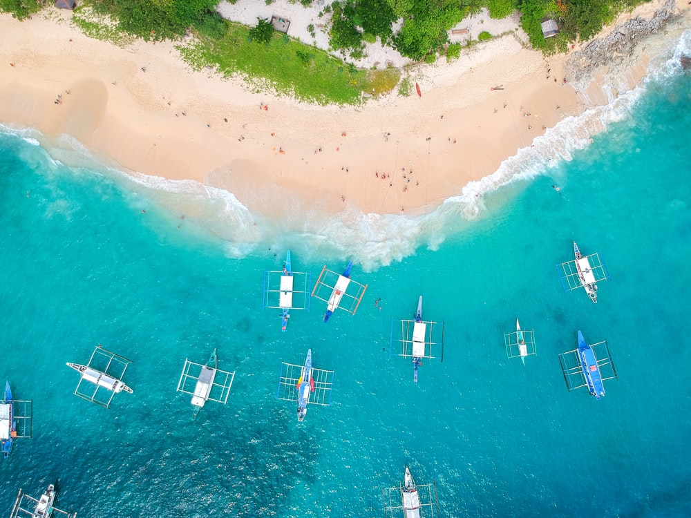 bird's-eye photography of boats on body of water near islet
