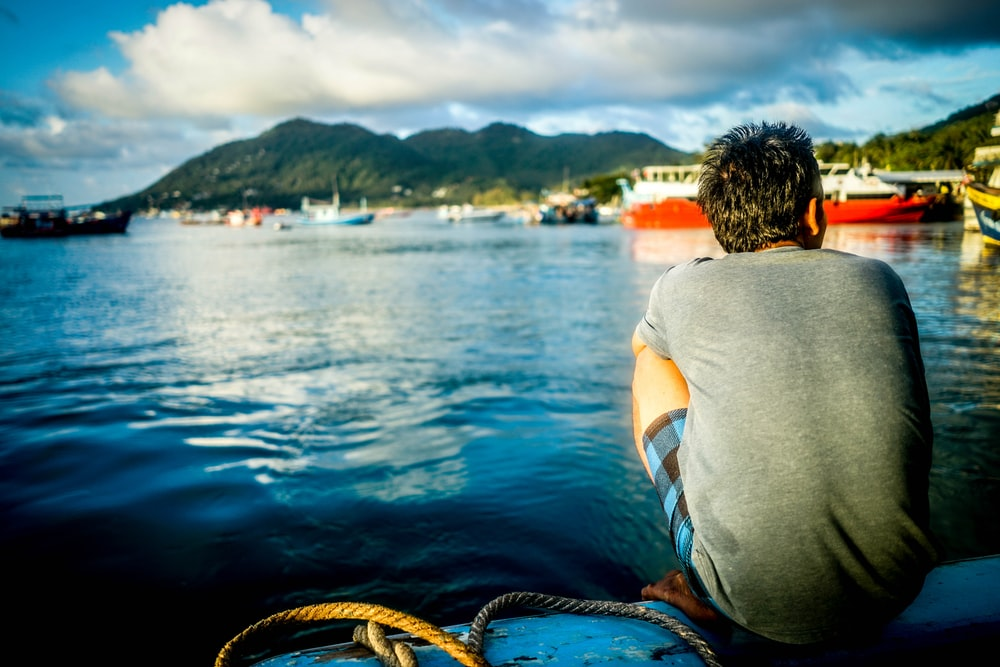 man sitting on boat in body of water