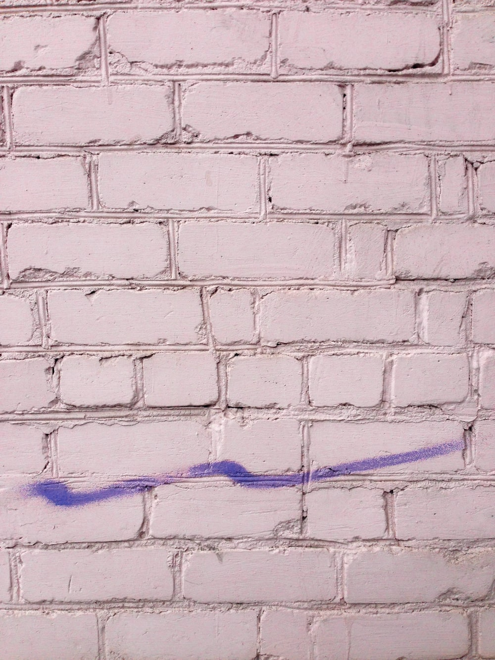 purple painting on white brick