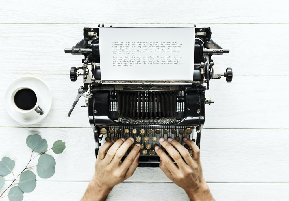 person using typewriter near white ceramic cup filled with coffee