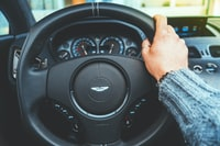 person holding onto a steering wheel