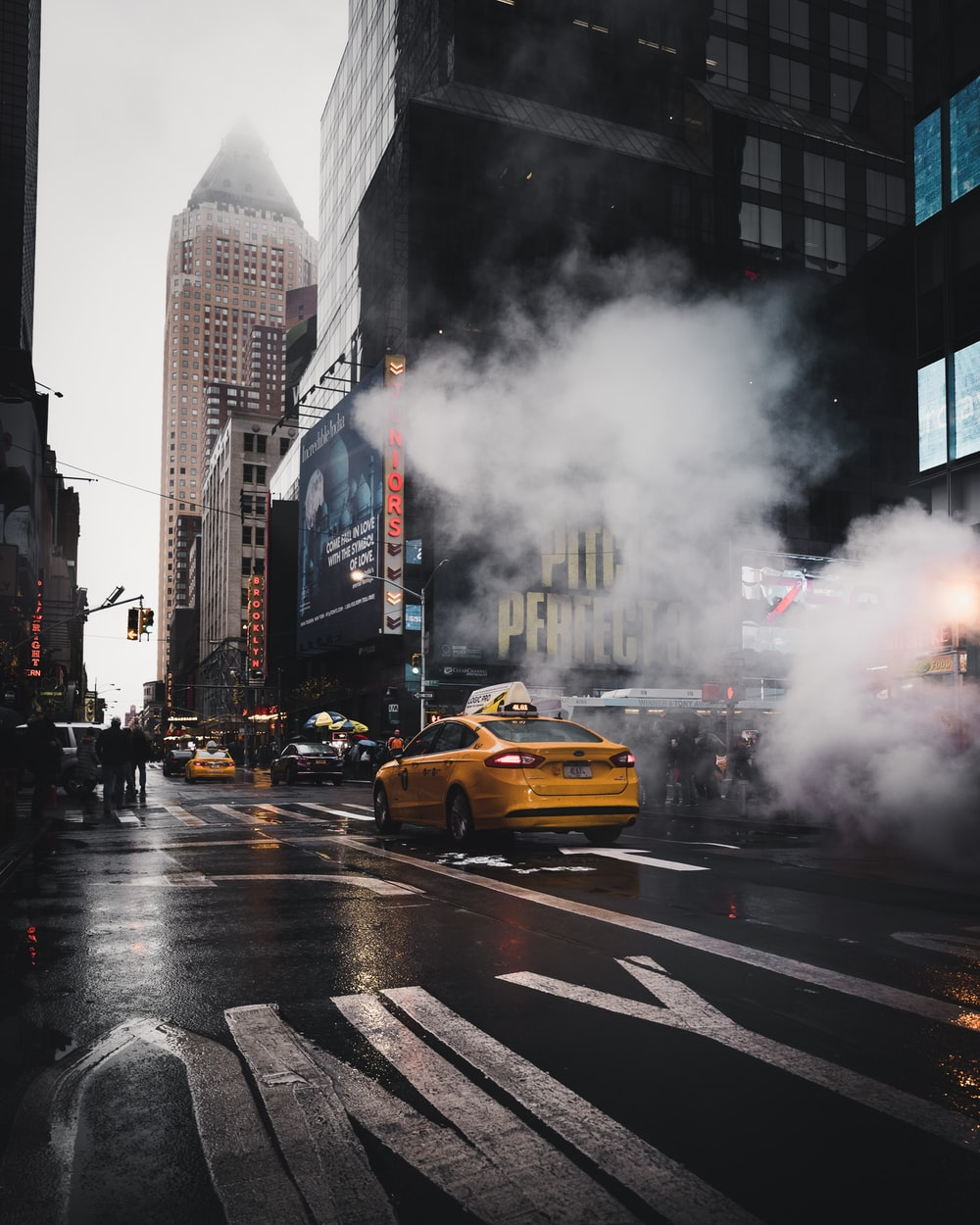 yellow taxi sedan on gray concrete street passed through white smokes near walking lane