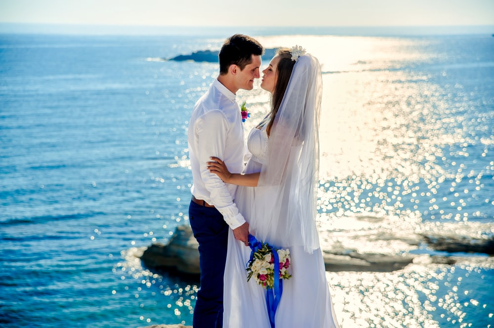 woman in wedding gown about to kiss man in white dress shirt while holding bouquet of flower near body of water at daytime