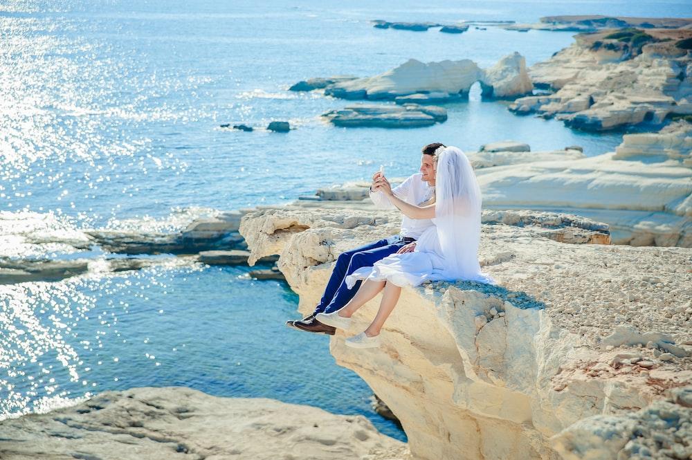 woman wearing wedding dress sitting beside man wearing white dress shirt on the stone tip facing the sea