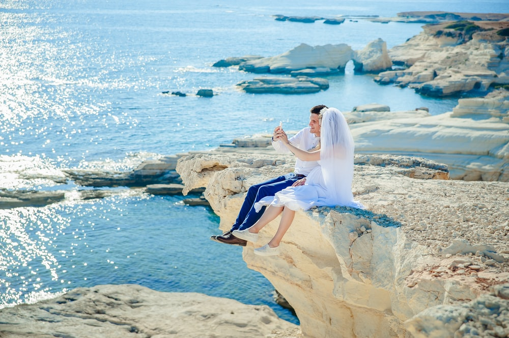 woman wearing wedding dress sitting beside man wearing white dress shirt on the stone tip facing the sea