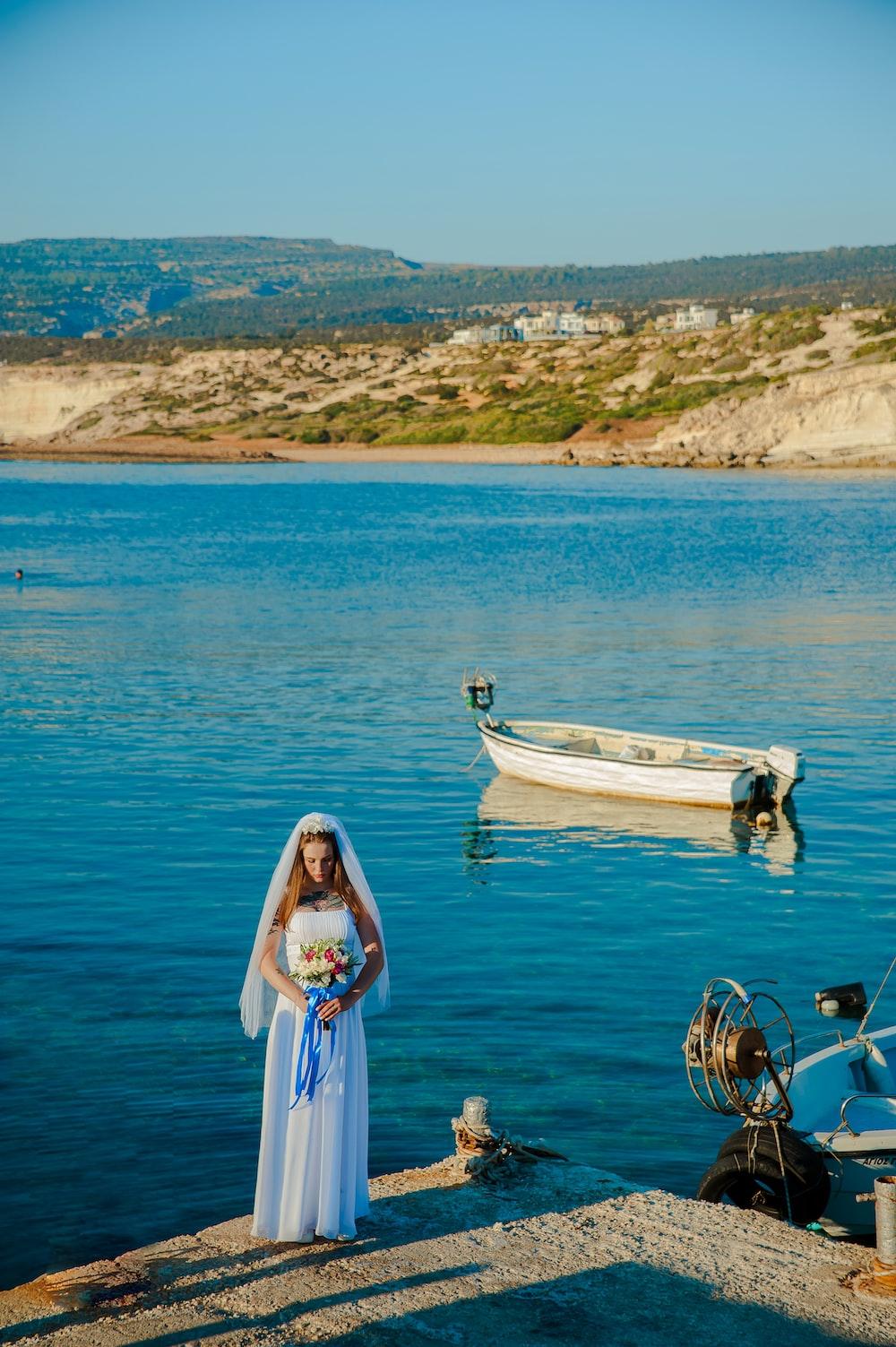 woman wearing white wedding dress standing near body of water holding flower bouquet