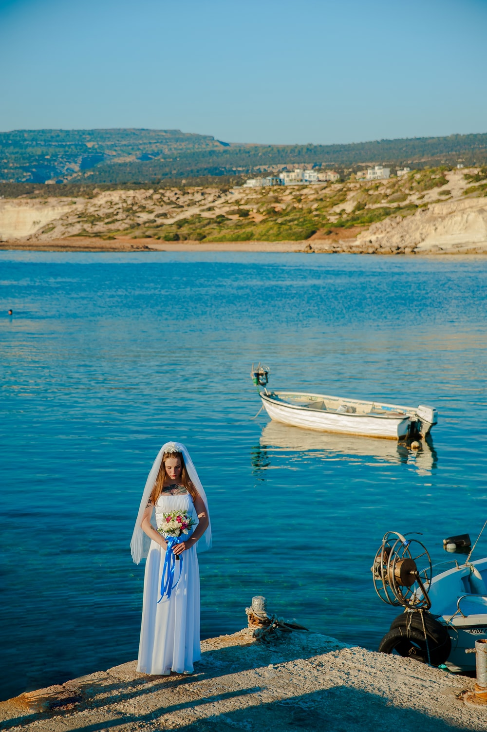 woman wearing white wedding dress standing near body of water holding flower bouquet