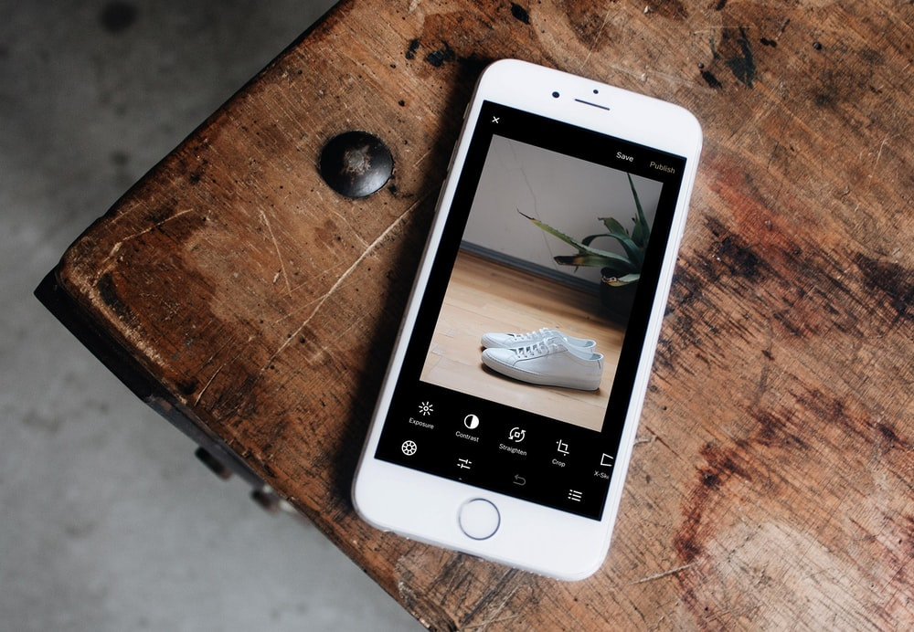 silver iPhone 6 displaying pair of white sneakers