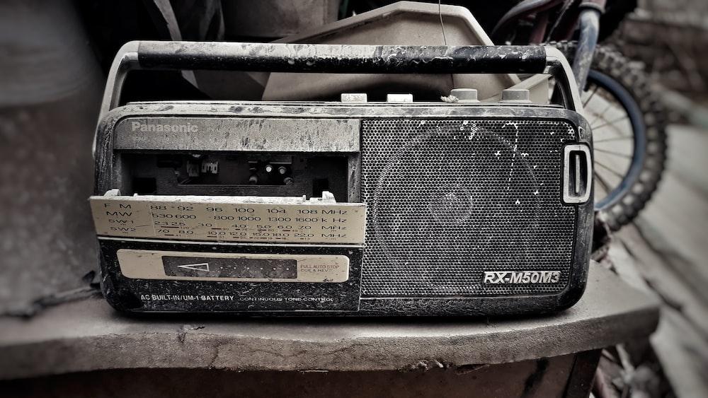 grey and black Panasonic RX-M50M3 transistor radio on grey surface