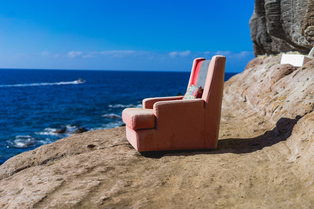 pink sofa chair near body of water