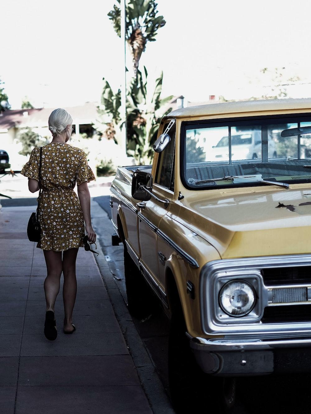 woman walking beside a car
